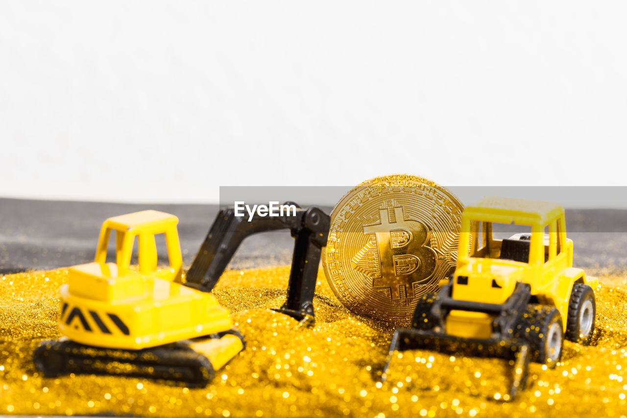 yellow, close-up, still life, toy, no people, toy car, car, studio shot, copy space, selective focus, indoors, mode of transportation, motor vehicle, land vehicle, transportation, bulldozer, communication, white background, table