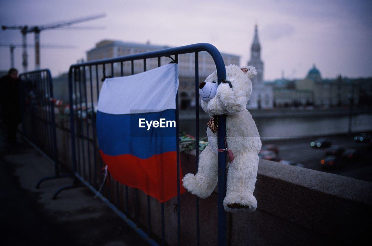 Teddy Bear And Russian Flag On Barricade Against Buildings In City