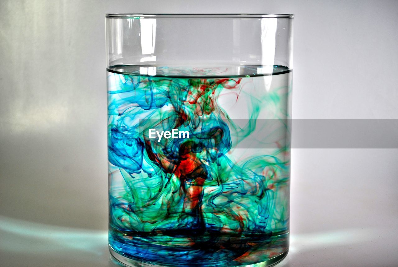 Close-Up Of Multi Colored Dissolving Water On Table