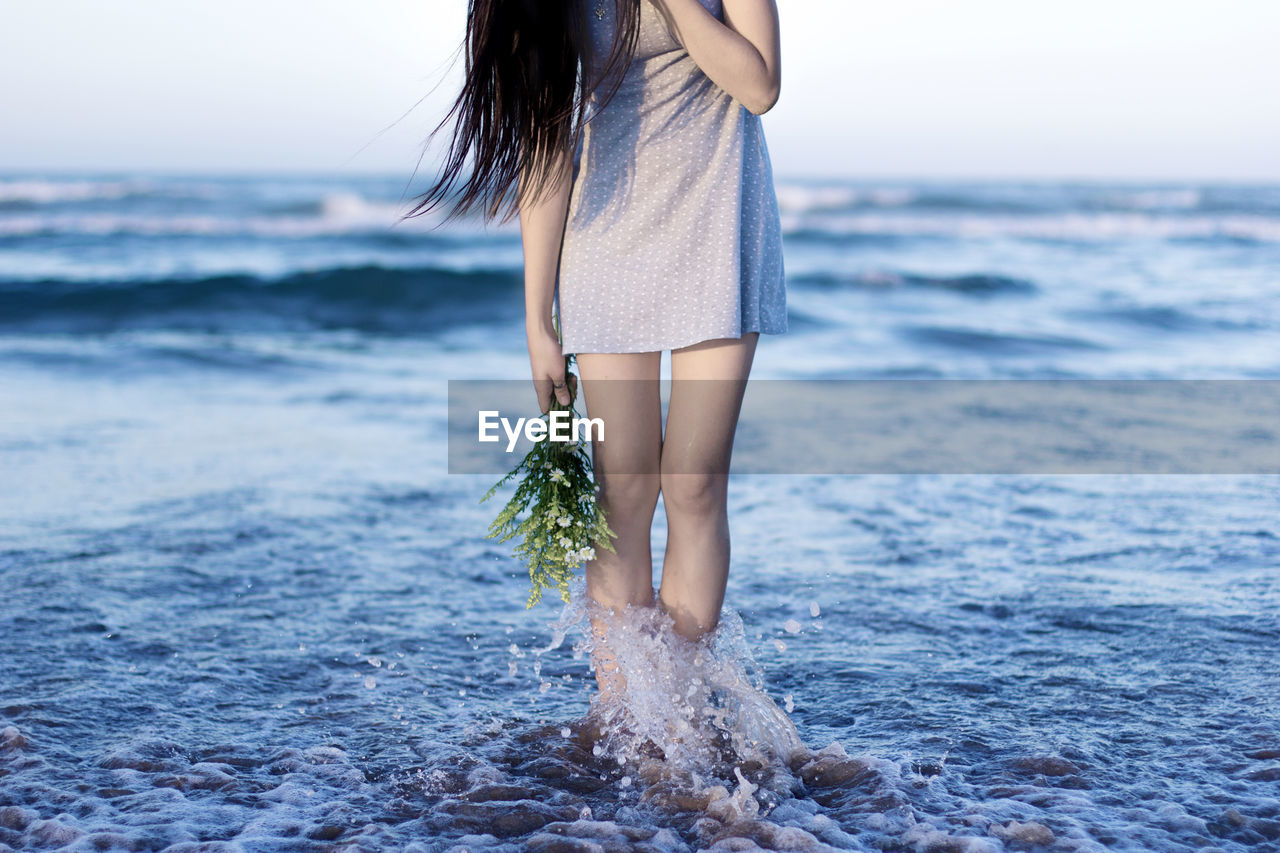 Low section of woman standing at beach against sky