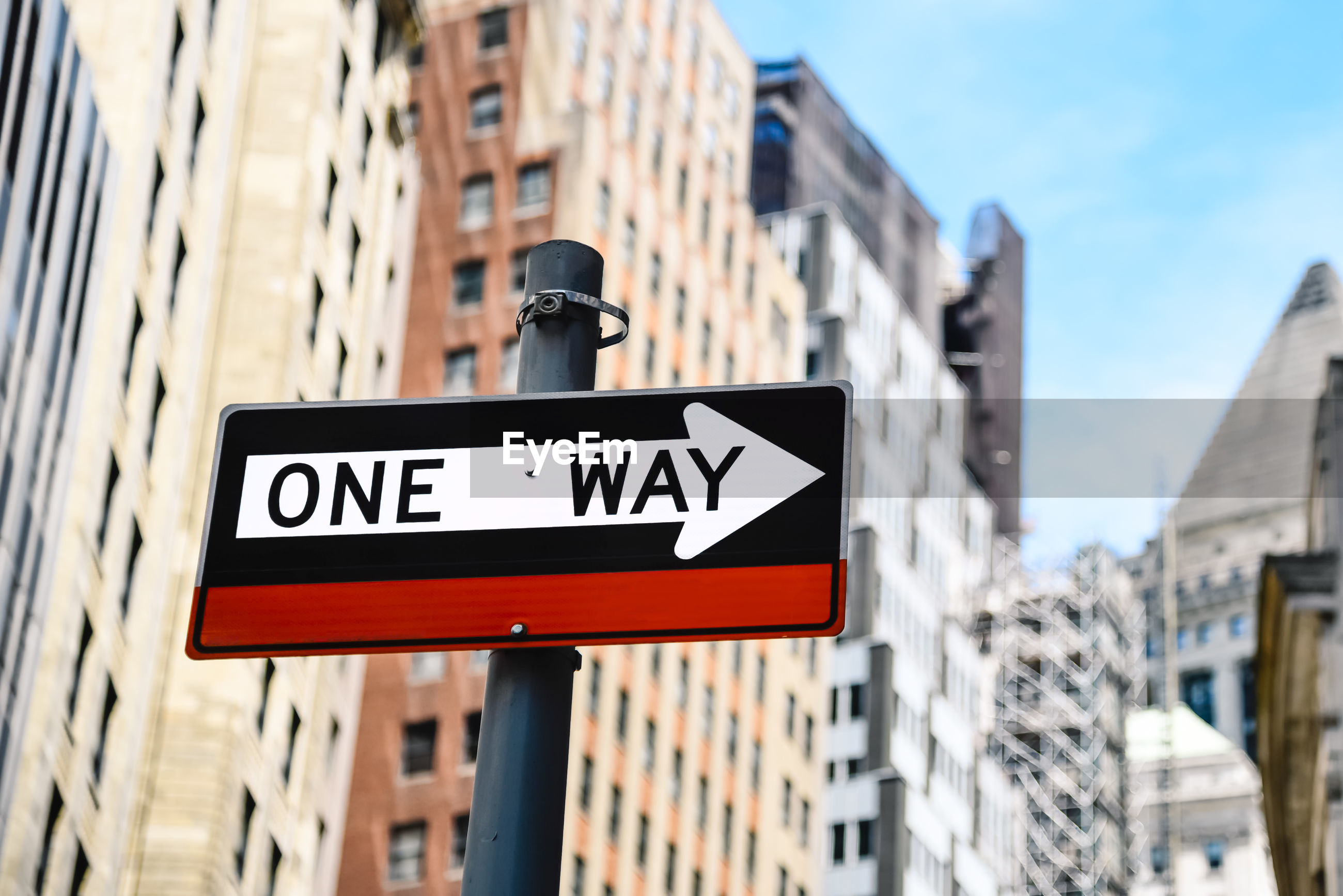 Low angle view of one way sign in city