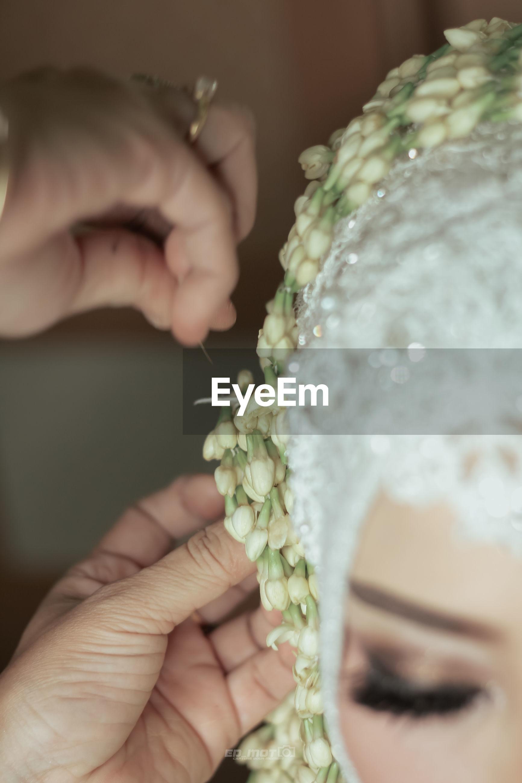 Cropped hands adjusting flowers in bride head
