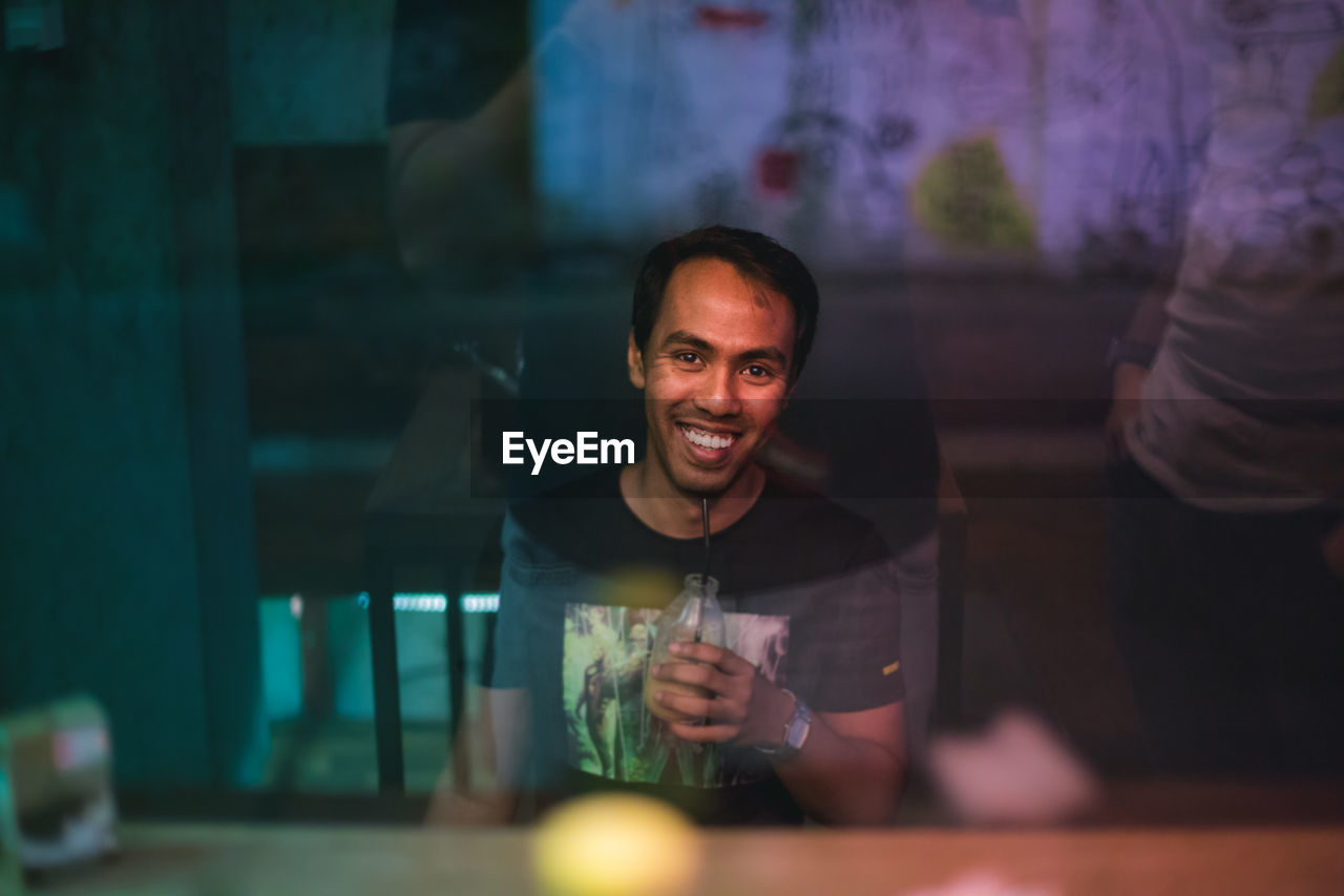 Portrait Of Young Man Having Drink While Sitting At Cafe See Through Window