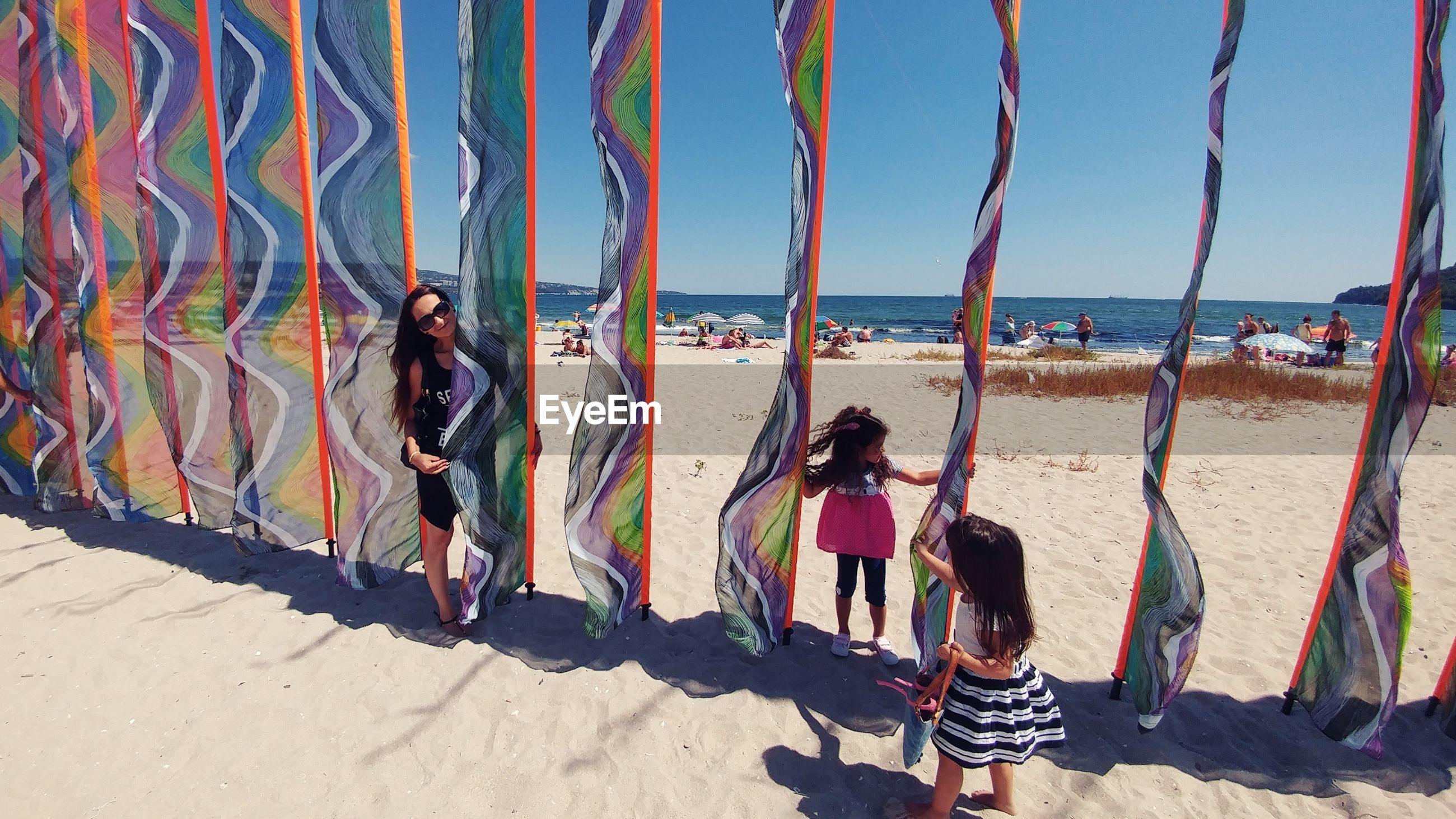 Mother with daughters playing at beach against clear sky during sunny day