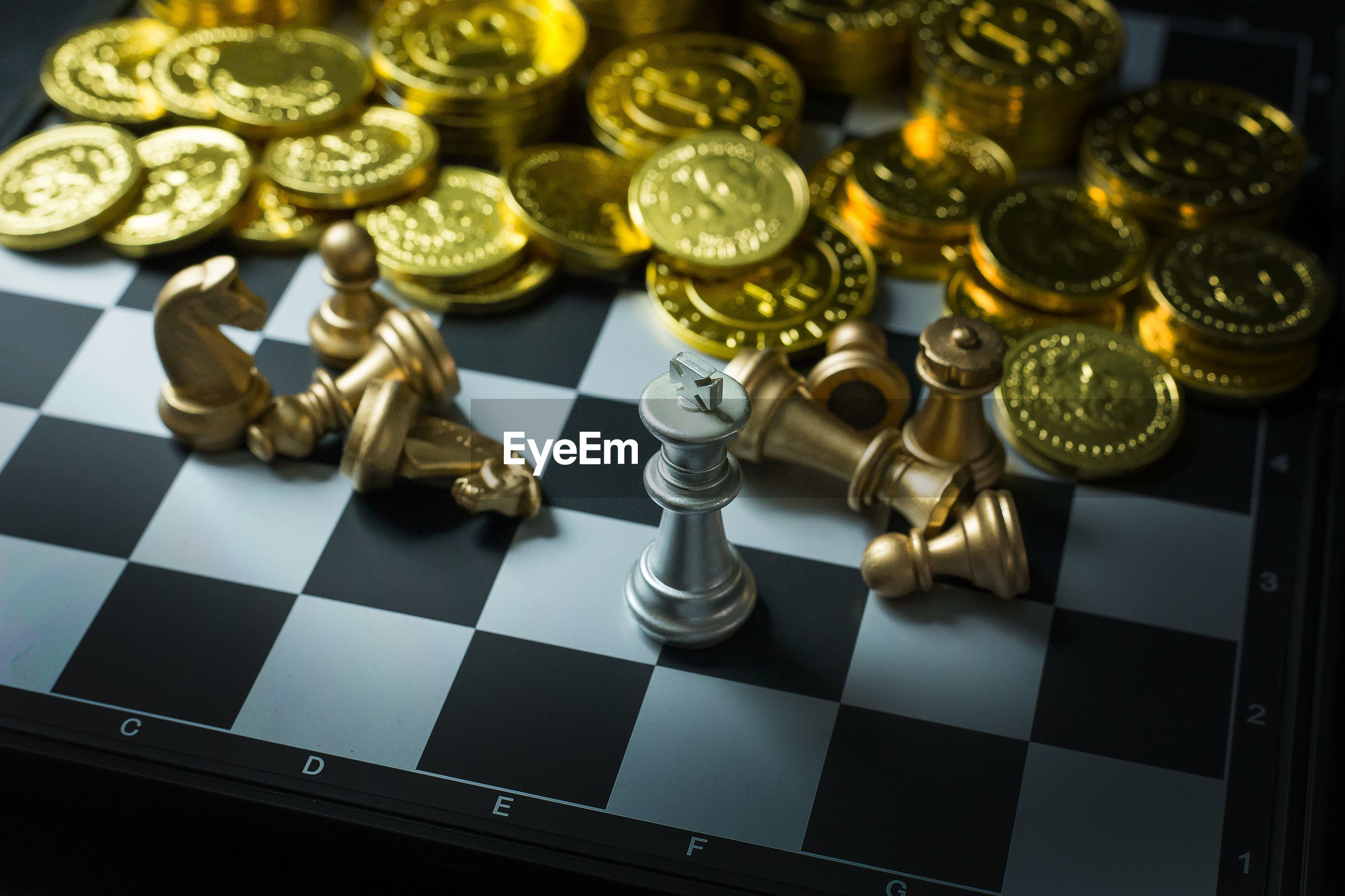 Close-up of chess pieces and coins on board