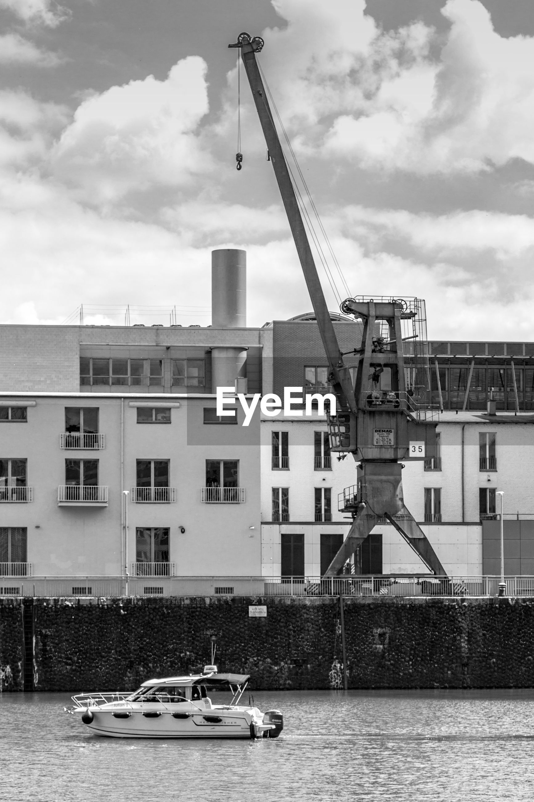 building exterior, architecture, crane - construction machinery, built structure, waterfront, development, transportation, water, sky, mode of transport, crane, cloud - sky, day, commercial dock, industry, outdoors, harbor, no people, tall - high, cloudy