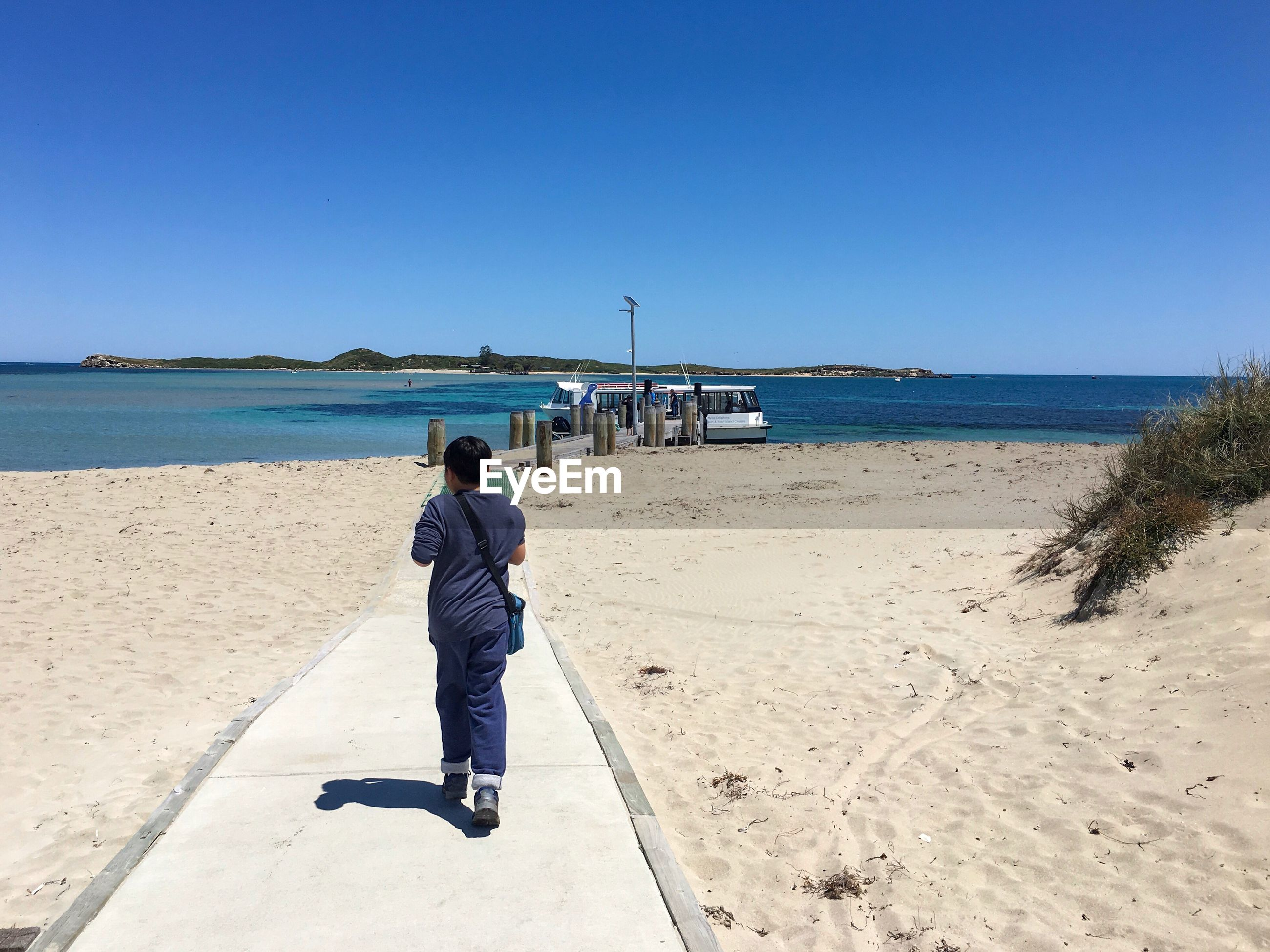 Rear view full length of boy on walkway at beach during sunny day