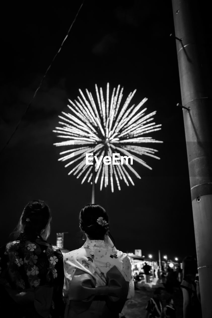 Rear view of women looking at firework display against sky