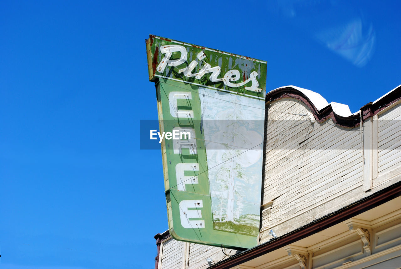 Low angle view of signboard outside cafe against sky