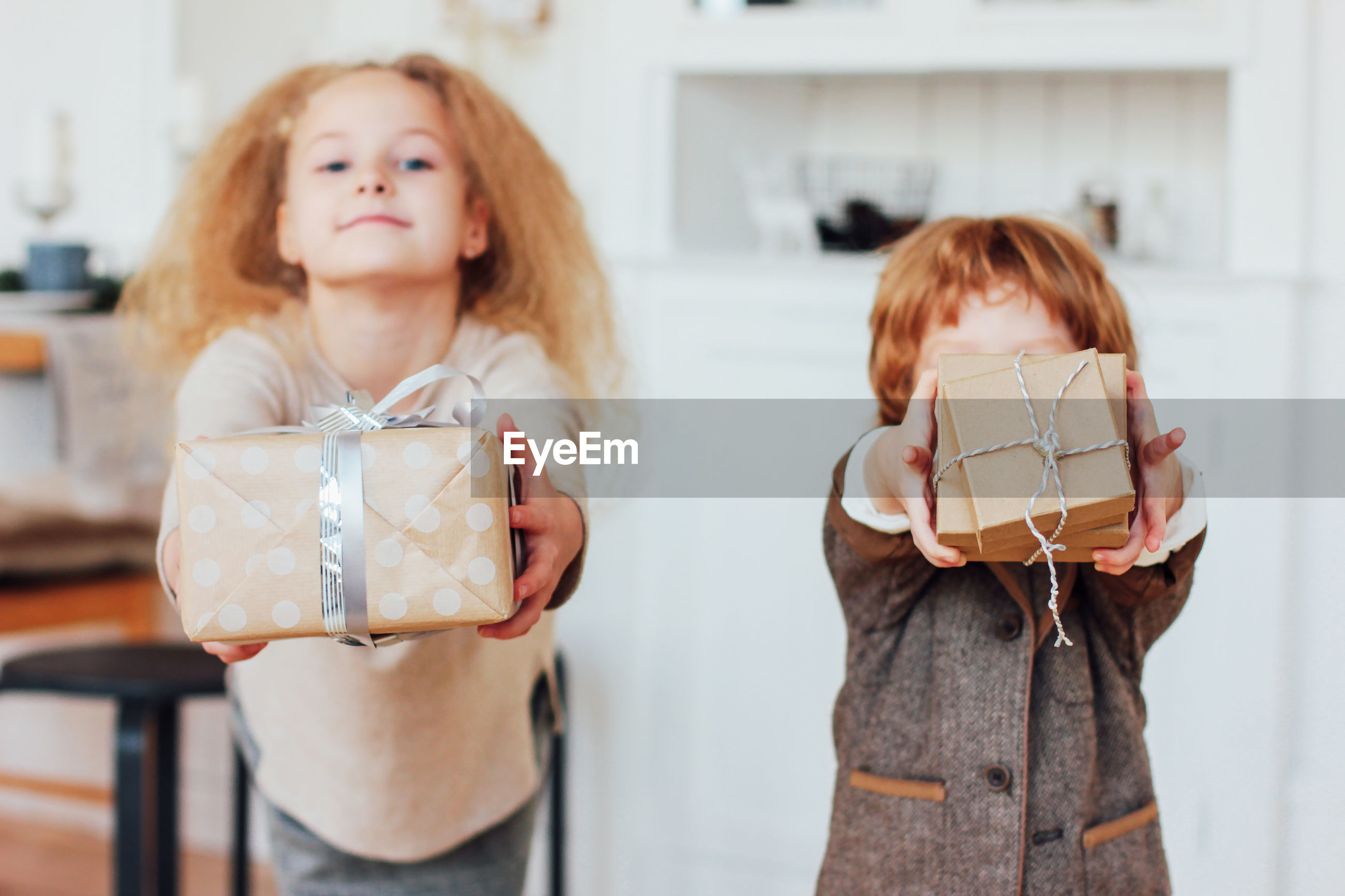 Cute siblings holding gifts at home
