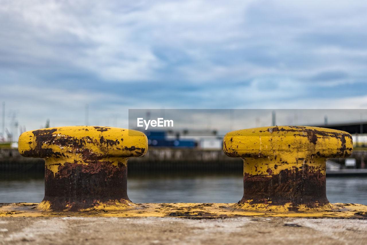 Rusty Yellow Bollards At Harbor