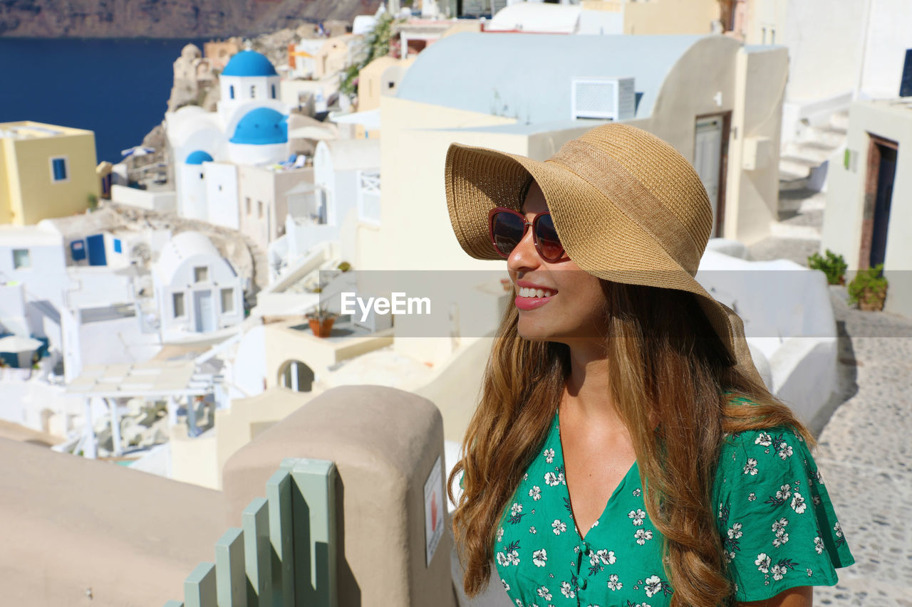 hat, one person, real people, women, smiling, leisure activity, focus on foreground, architecture, clothing, day, adult, lifestyles, built structure, happiness, front view, long hair, city, young women, headshot, hairstyle, fashion, hair, outdoors, sun hat, beautiful woman