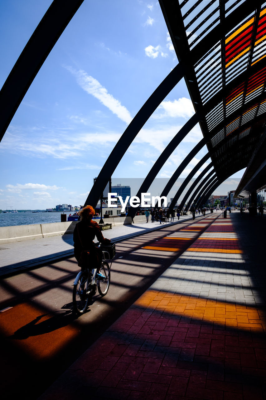 transportation, sky, architecture, mode of transportation, built structure, sunlight, shadow, bicycle, land vehicle, nature, cloud - sky, city, bridge, real people, building exterior, travel, bridge - man made structure, day, full length, one person, outdoors, riding