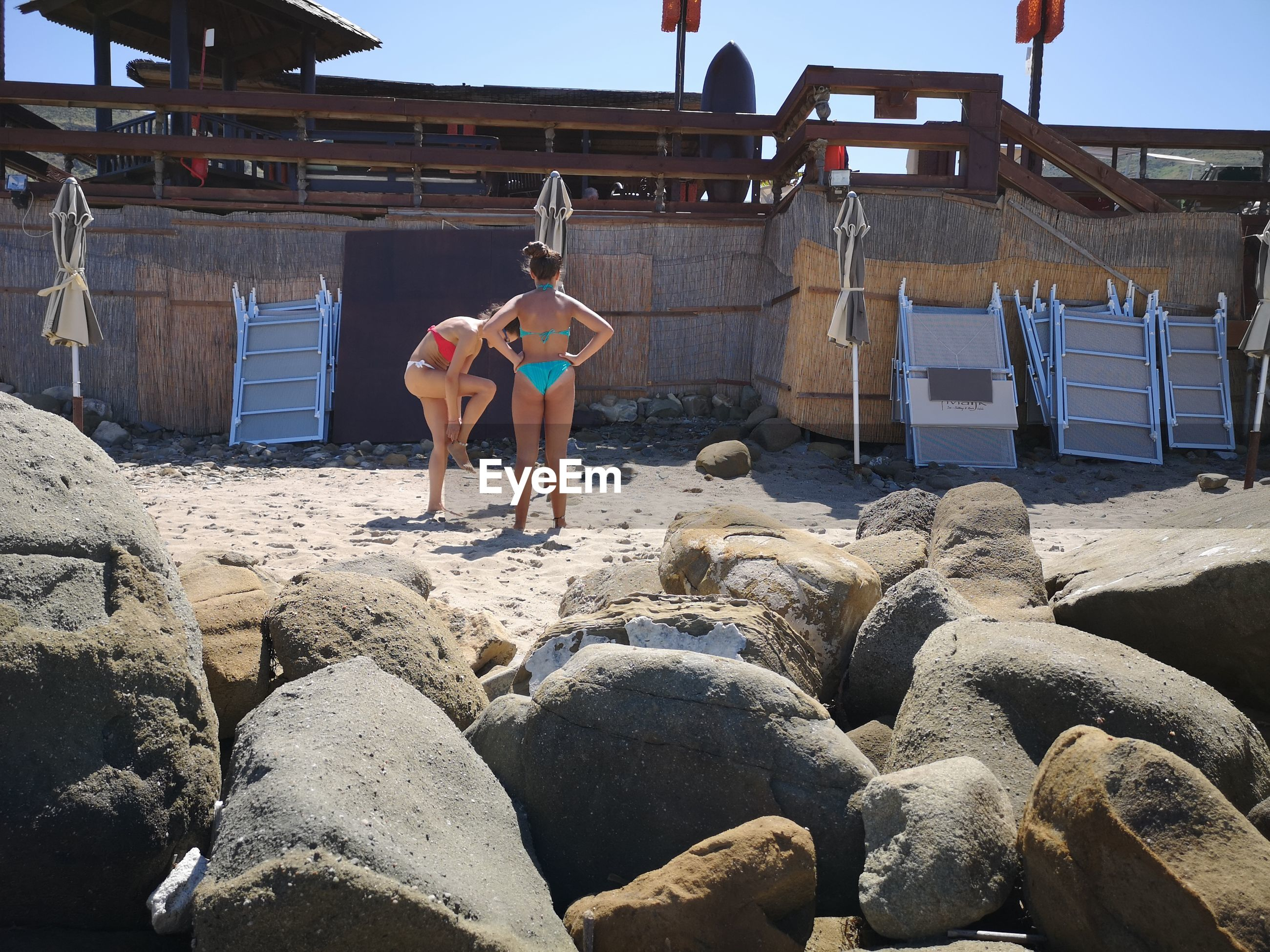 FULL LENGTH OF SHIRTLESS MAN STANDING ON ROCKS BY BUILDING