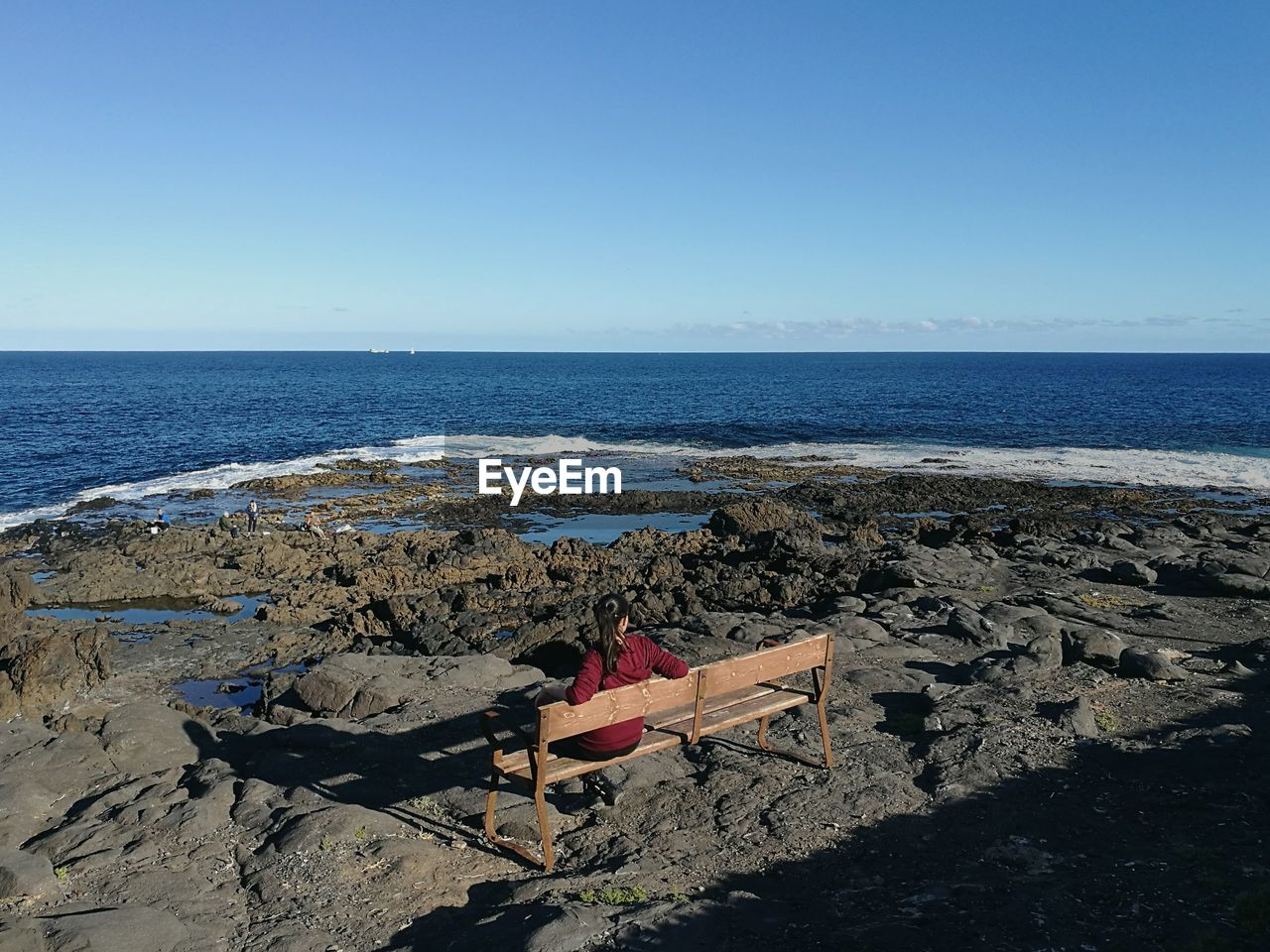 Rear View Of Woman Sitting On Bench At Rocky Shore Against Clear Blue Sky