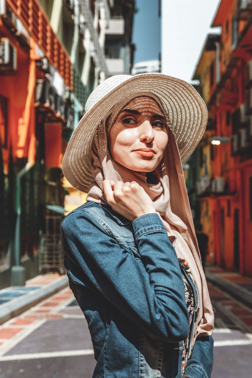 one person, architecture, clothing, hat, city, building exterior, built structure, real people, young adult, standing, lifestyles, portrait, casual clothing, young women, looking at camera, front view, focus on foreground, leisure activity, day, beautiful woman, outdoors, hairstyle, warm clothing