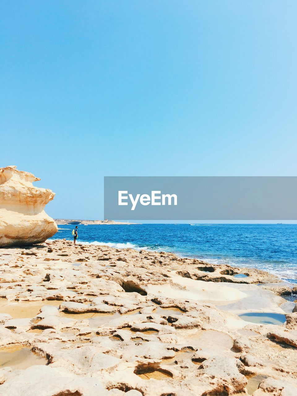 Mid Distant View Of Man Standing By Rock At Beach Against Clear Blue Sky