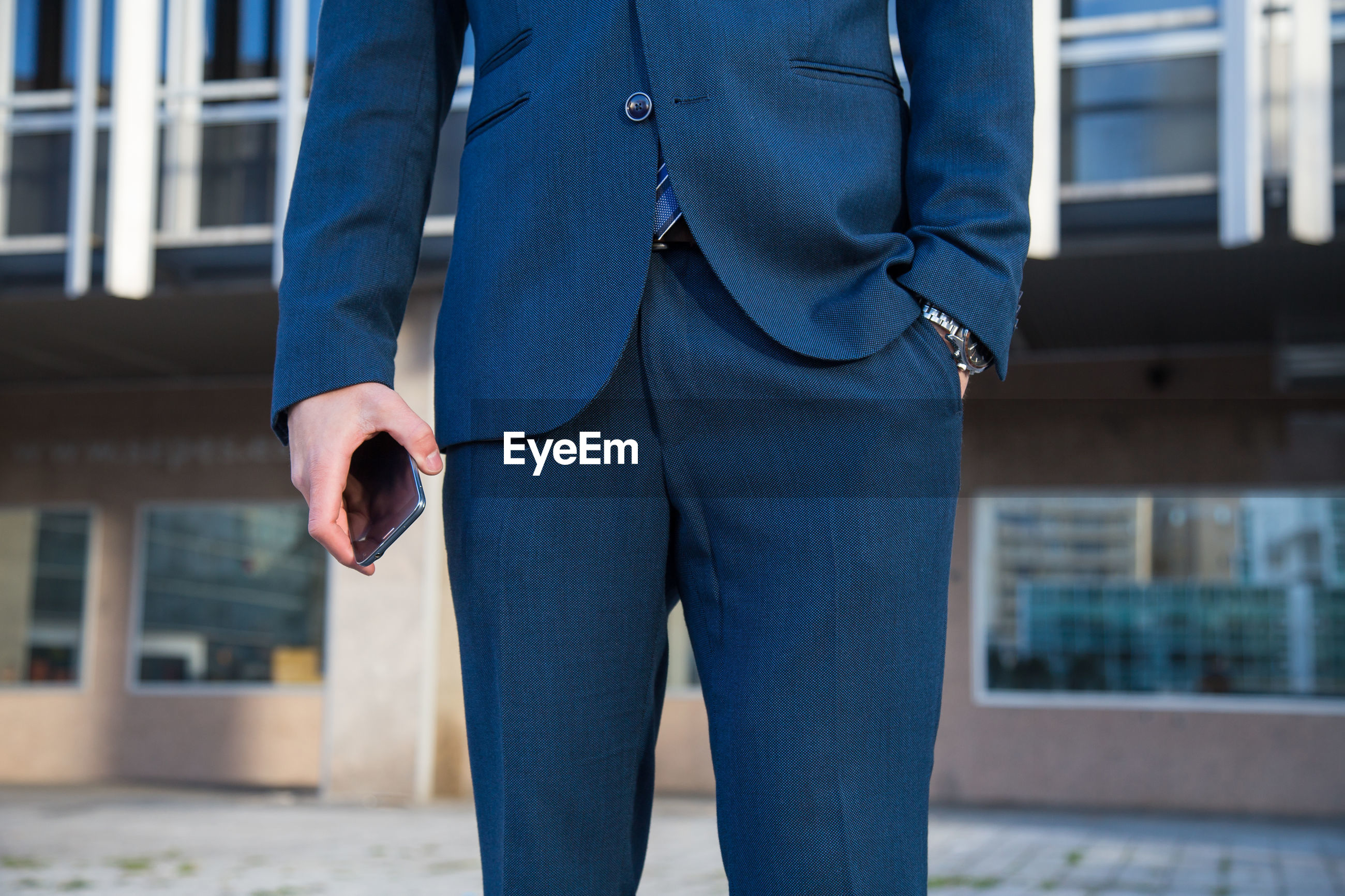 Midsection of businessman holding mobile phone while standing in city
