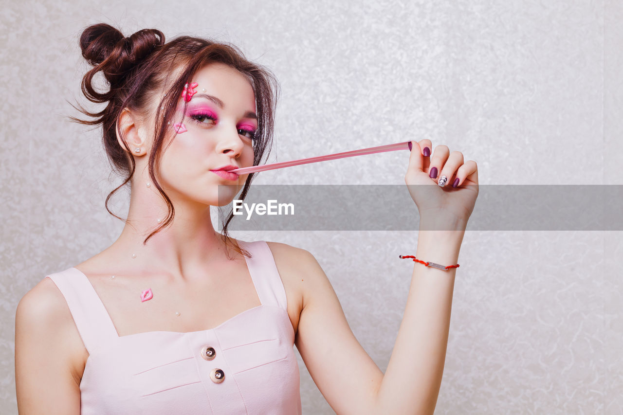 Young woman with pink make-up chewing gum against wall