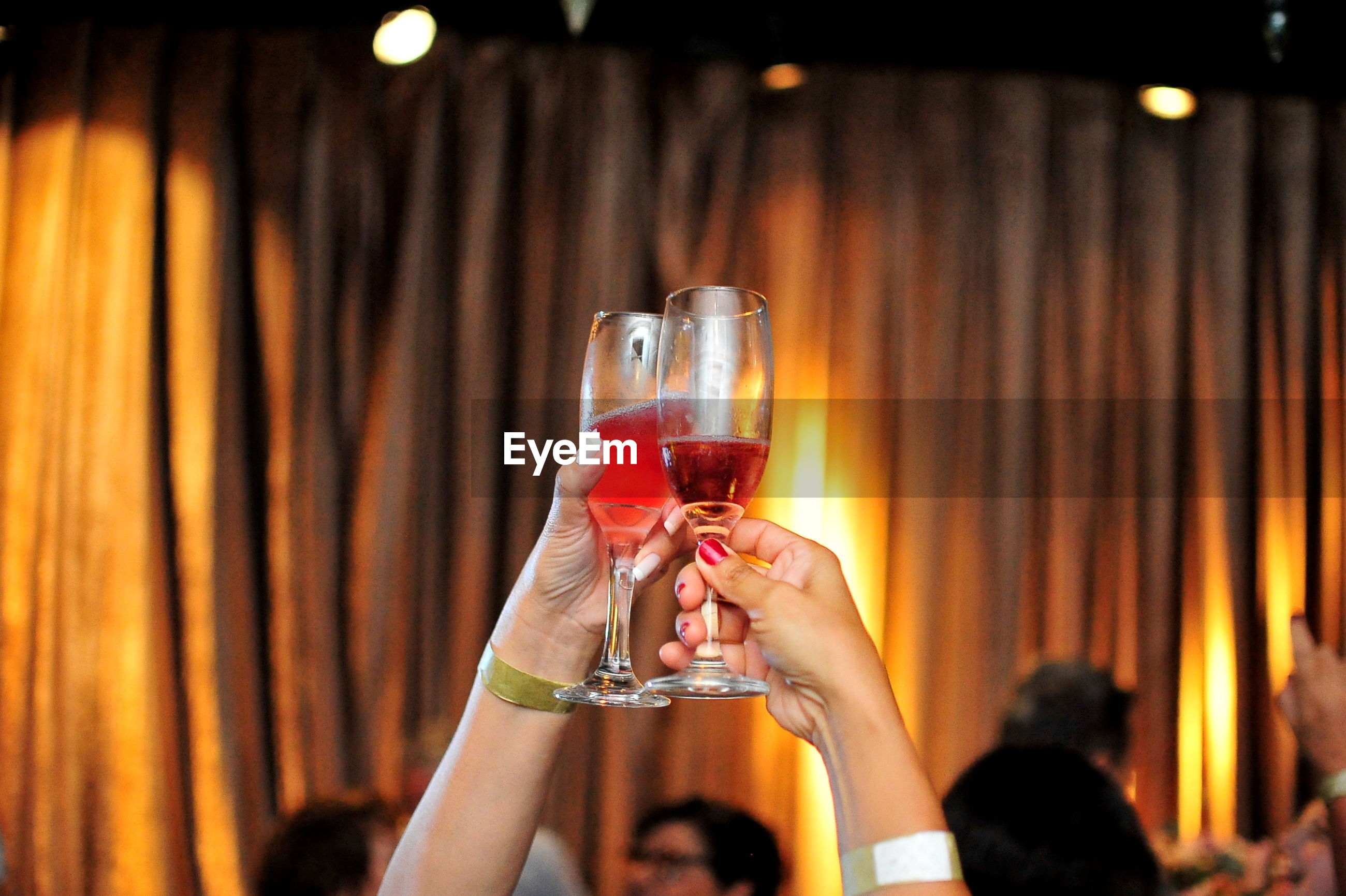 Cropped image of hands toasting drinks at party