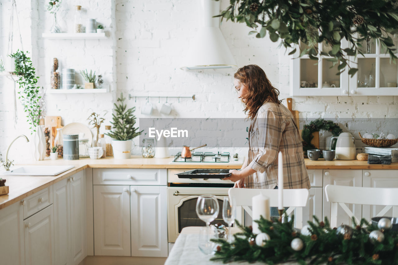 Attractive smiling woman with curly hair in plaid shirt bakes cookies at bright kitchen at home