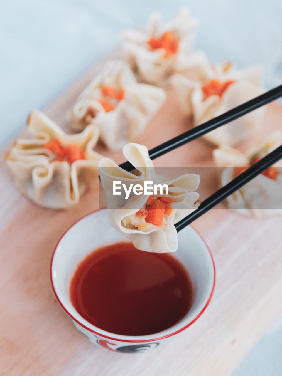 Close-up of chinese dimsum on wood chopper board with hot sauce