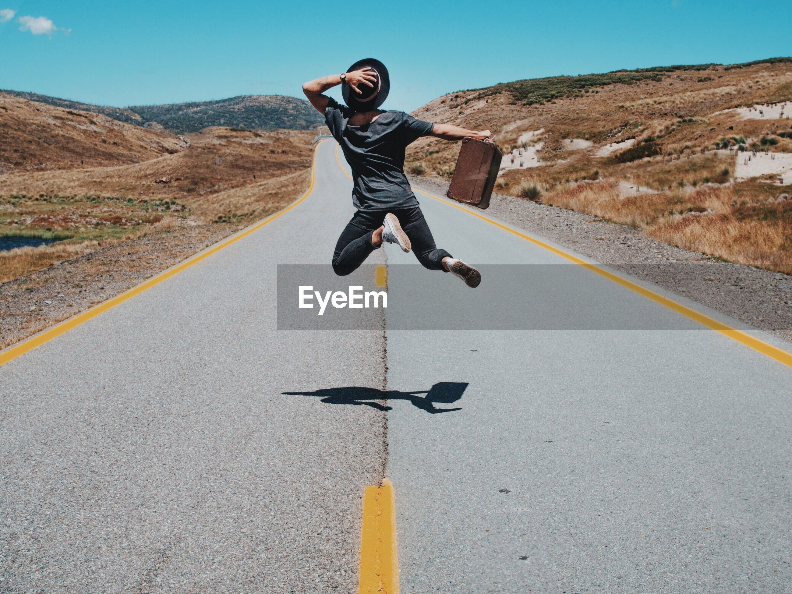 Rear view of man jumping on country road against sky