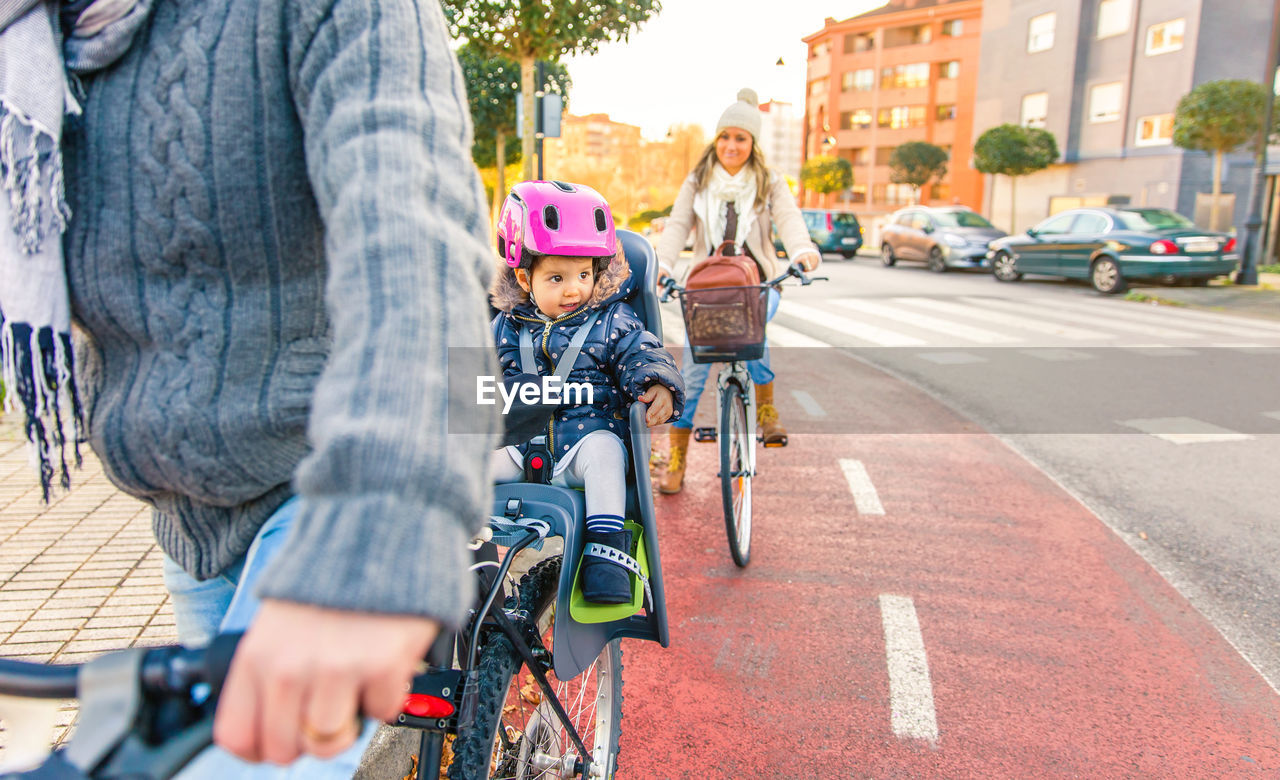 Family Riding Bicycles On Street In City