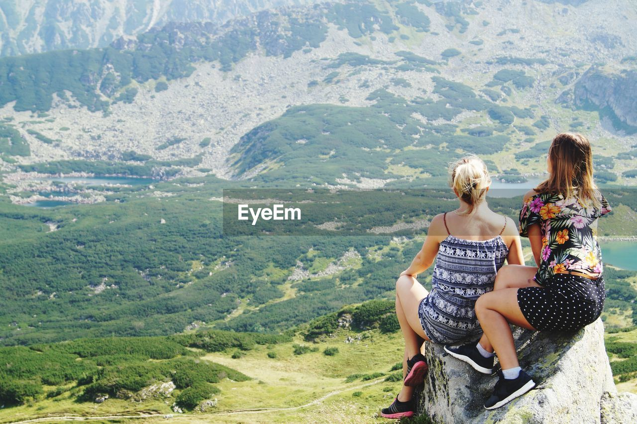 two people, leisure activity, rear view, togetherness, women, casual clothing, sitting, full length, nature, mountain, girls, day, females, family, lifestyles, childhood, people, real people, bonding, scenics - nature, hair, outdoors, looking at view, hairstyle, positive emotion