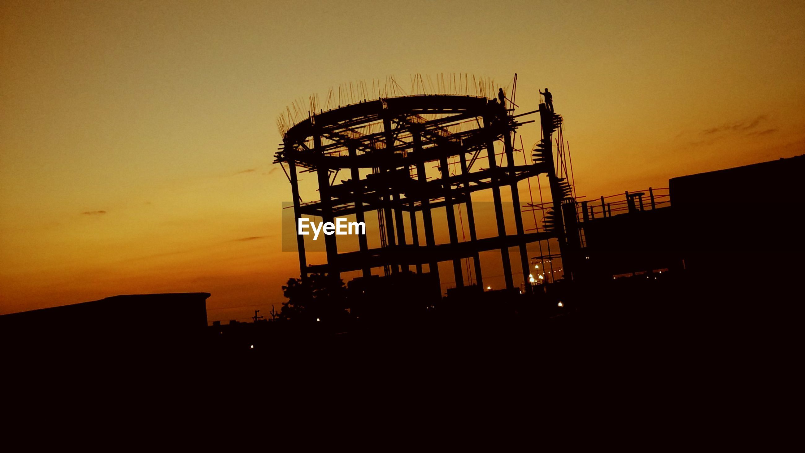 Silhouette workers at construction site against sky during sunset