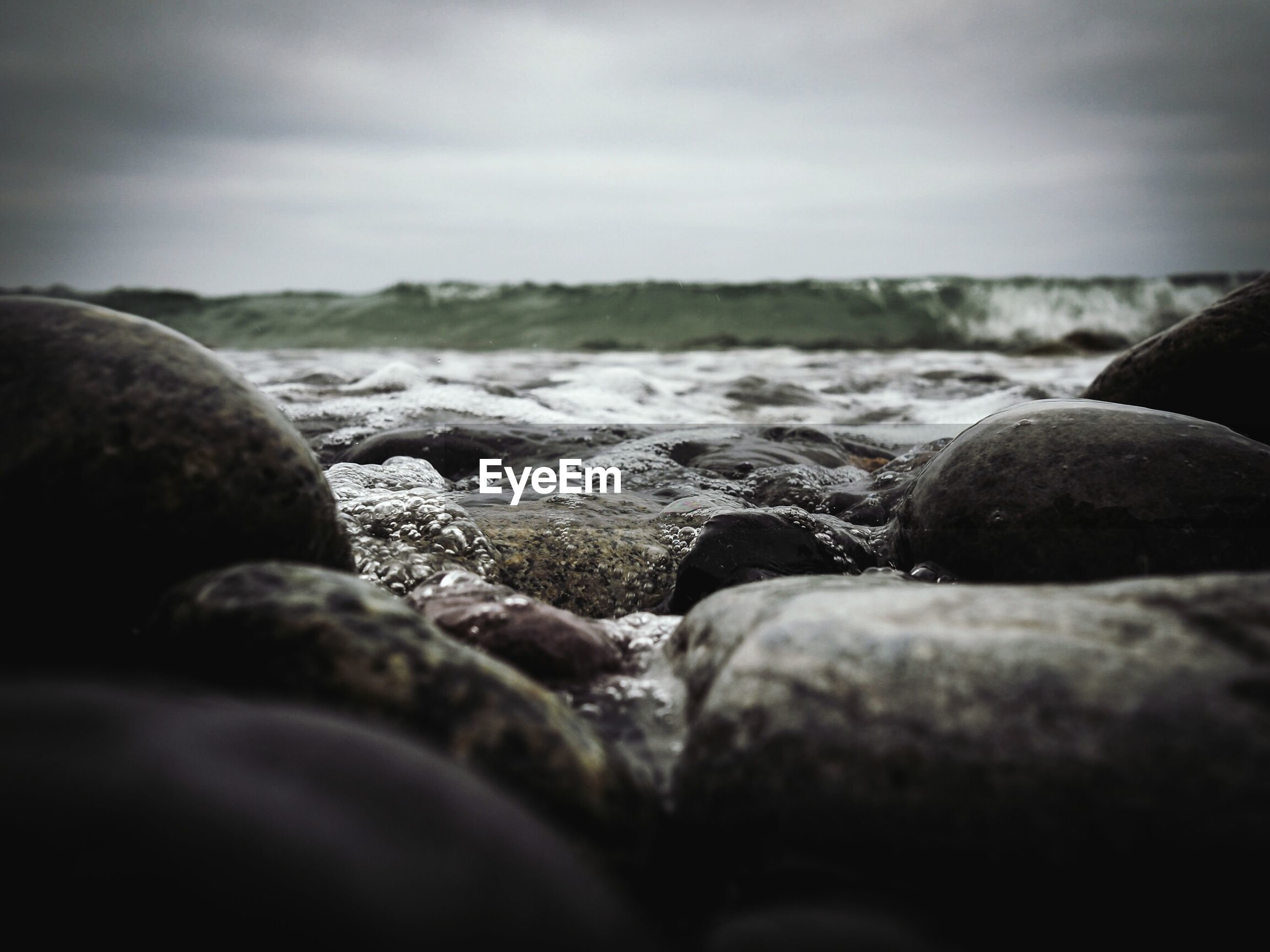 Surface level of rocks on lakeshore against sky