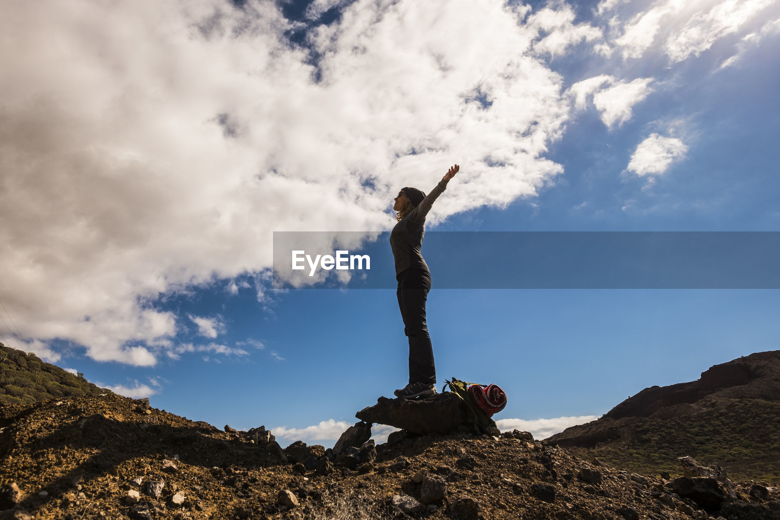 Low angle view of woman standing with arms outstretched on land against sky