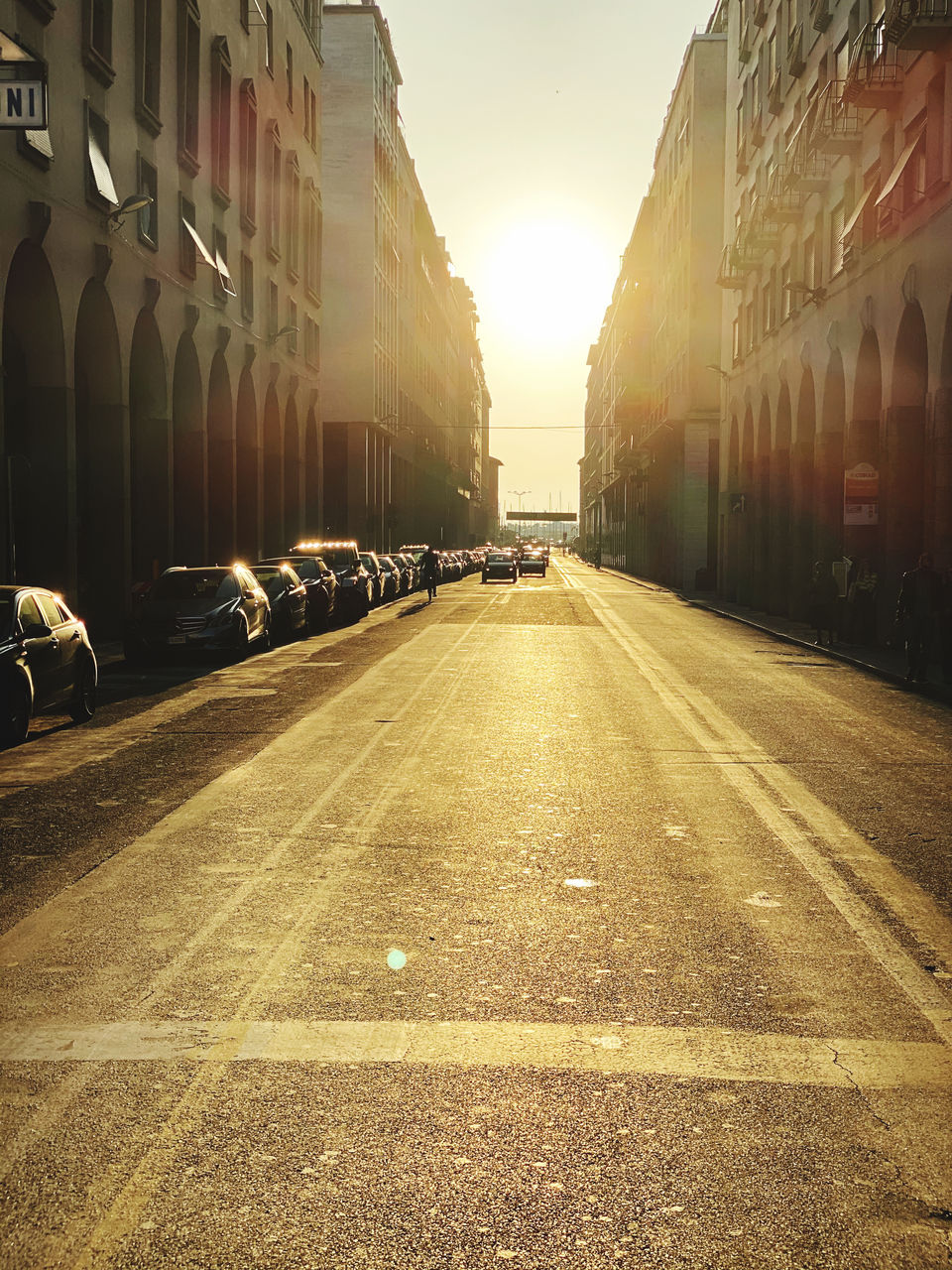 city, transportation, car, street, building exterior, motor vehicle, architecture, road, built structure, direction, mode of transportation, the way forward, land vehicle, sunlight, sky, nature, city street, building, symbol, diminishing perspective, no people, outdoors