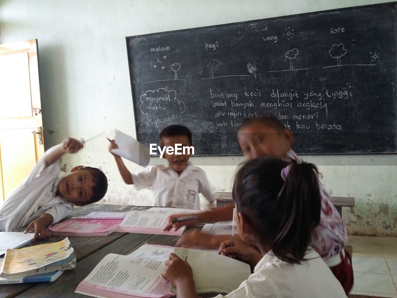 education, indoors, boys, childhood, elementary age, blackboard, learning, classroom, girls, real people, book, togetherness, men, headshot, day, teamwork, people
