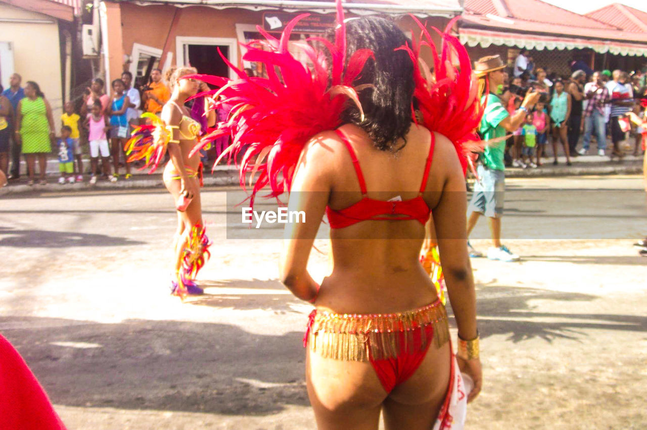 real people, lifestyles, leisure activity, performance, dancing, fun, day, celebration, arts culture and entertainment, outdoors, rear view, traditional festival, traditional dancing, sunlight, headdress, shadow, women, men, multi colored, young women, young adult, adult, adults only, people