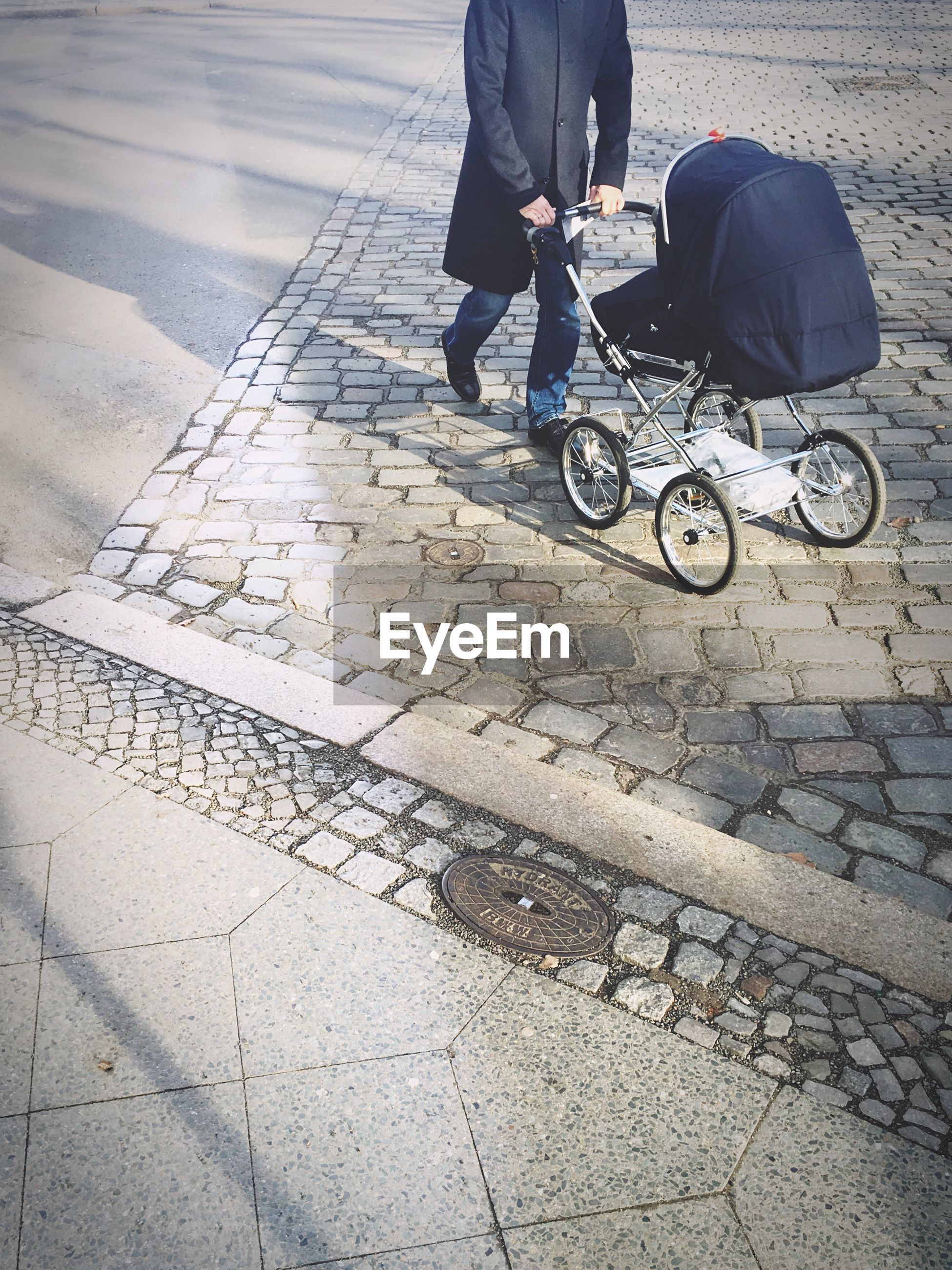 Low section of man walking with baby stroller on footpath
