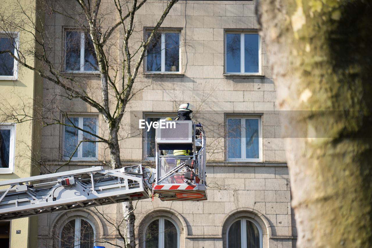 Man standing in cherry picker against building