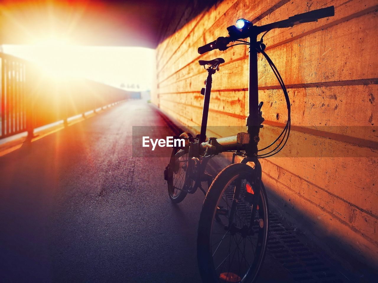 BICYCLE ON STREET IN CITY AGAINST SKY DURING SUNSET