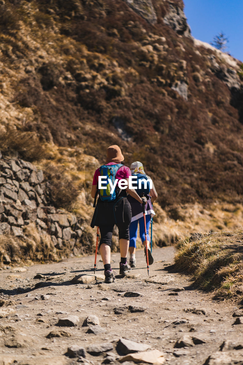 rear view, leisure activity, walking, lifestyles, real people, mountain, full length, hiking, nature, activity, backpack, women, land, day, two people, rock, togetherness, adventure, healthy lifestyle, people, outdoors