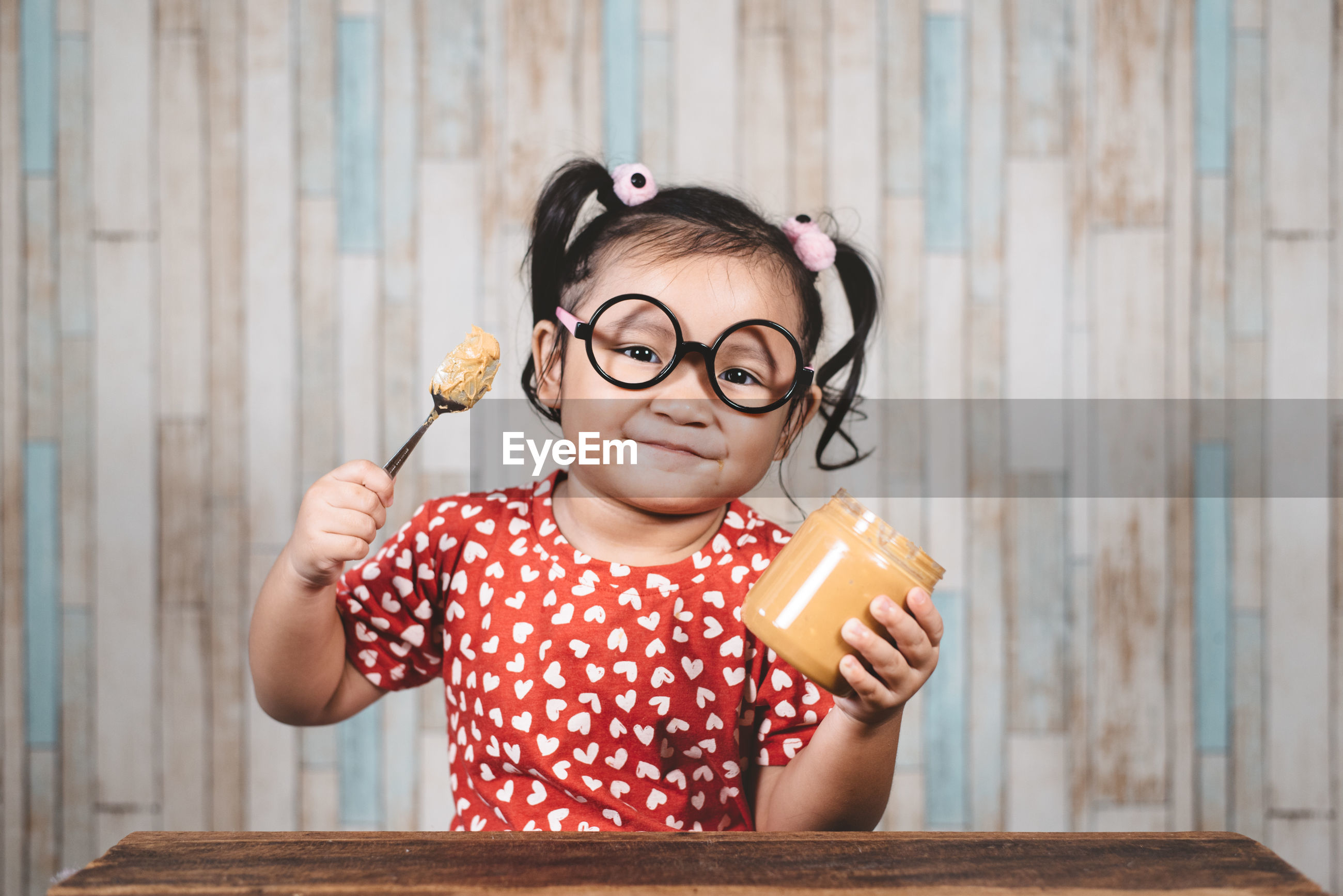 Portrait of happy girl holding spoon and peanut butter bottle