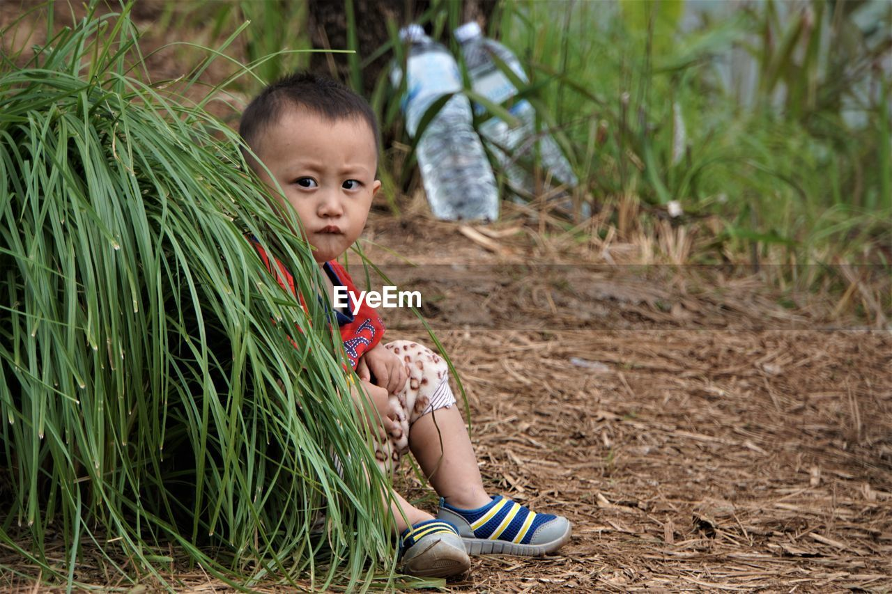 Portrait Of Smiling Boy Sitting On Field