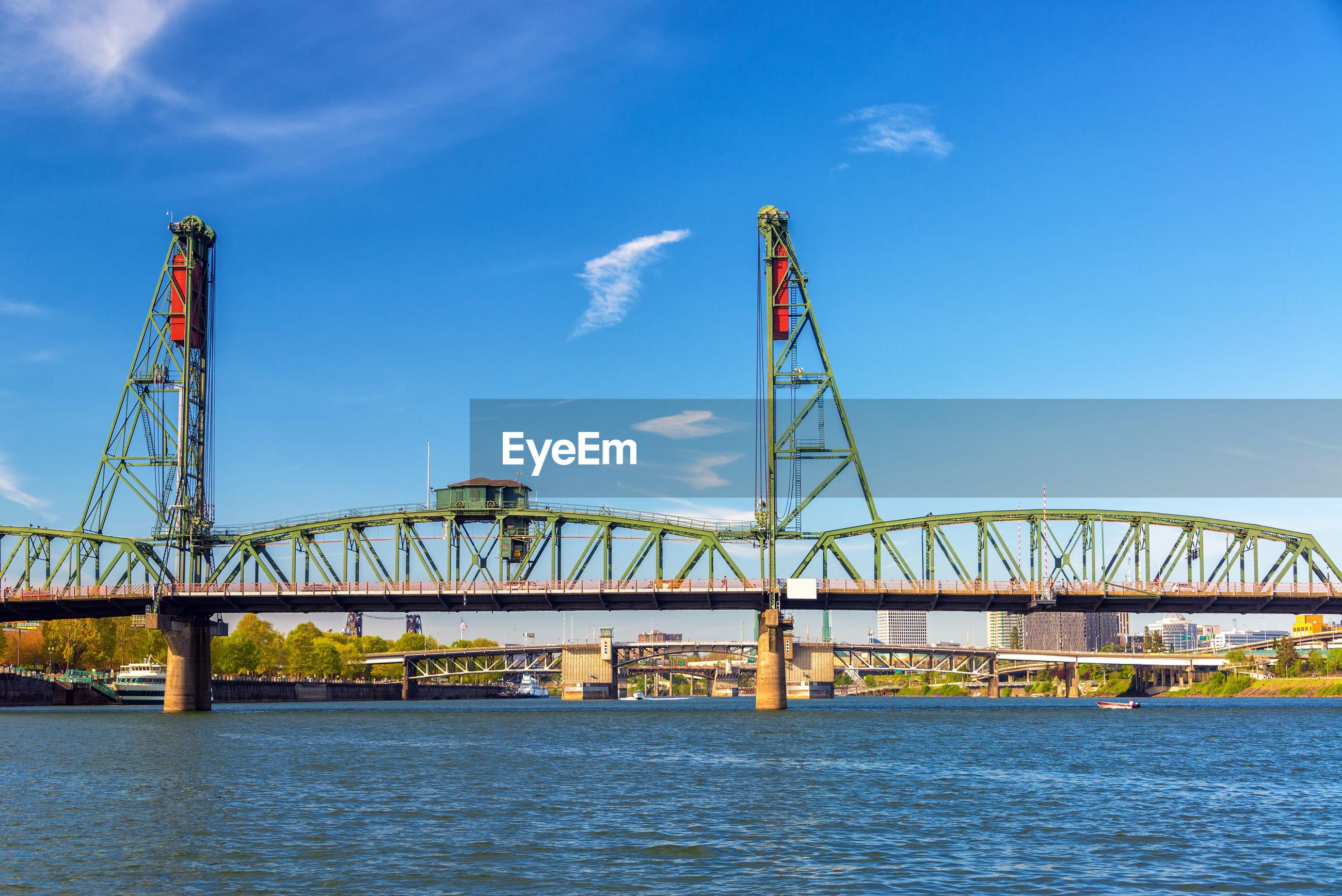 Hawthorne bridge over willamette river against blue sky in city