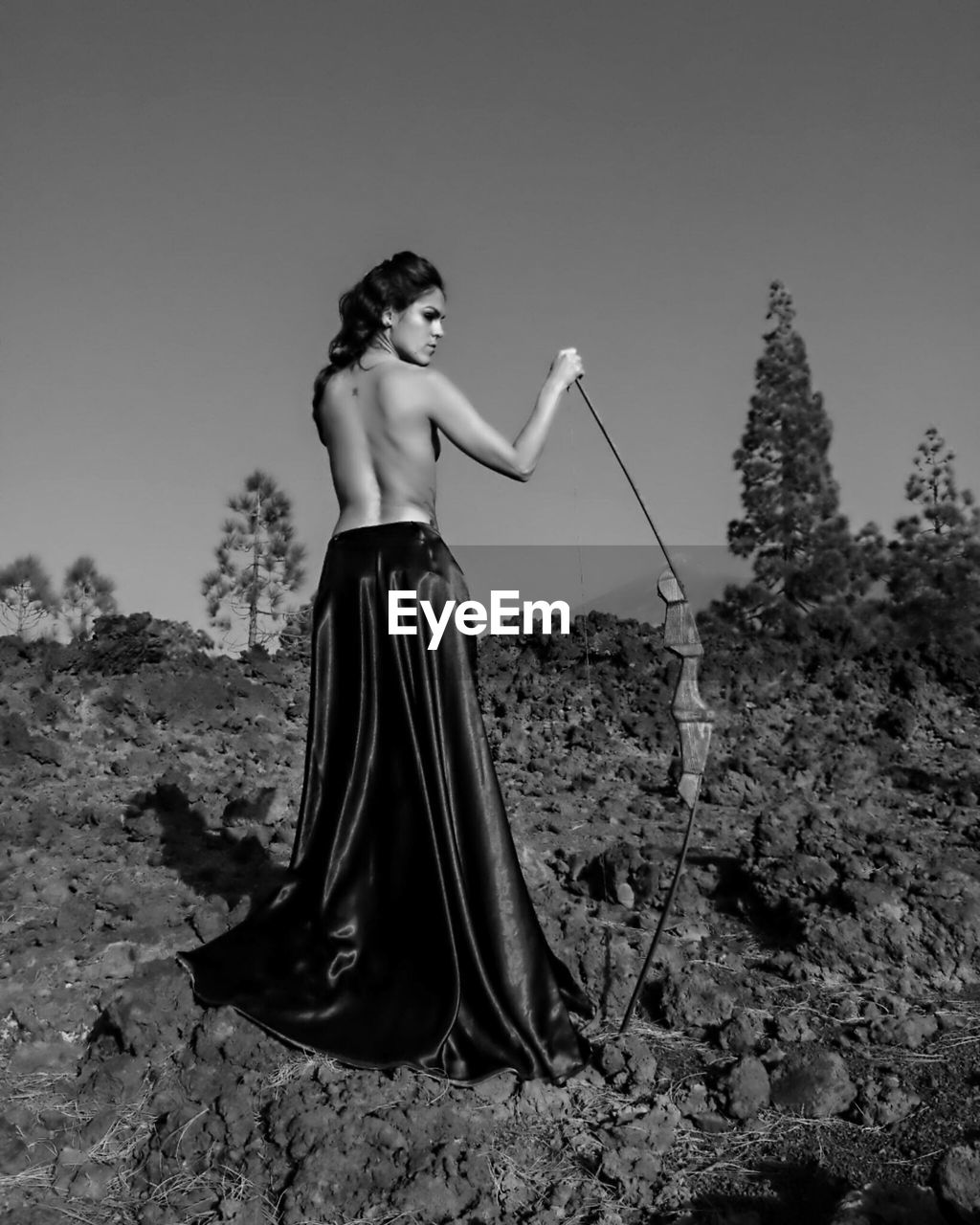 Rear View Of Topless Young Woman Holding Archery Bow While Standing On Field