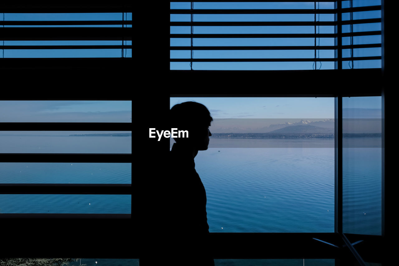 Man standing by window against lake