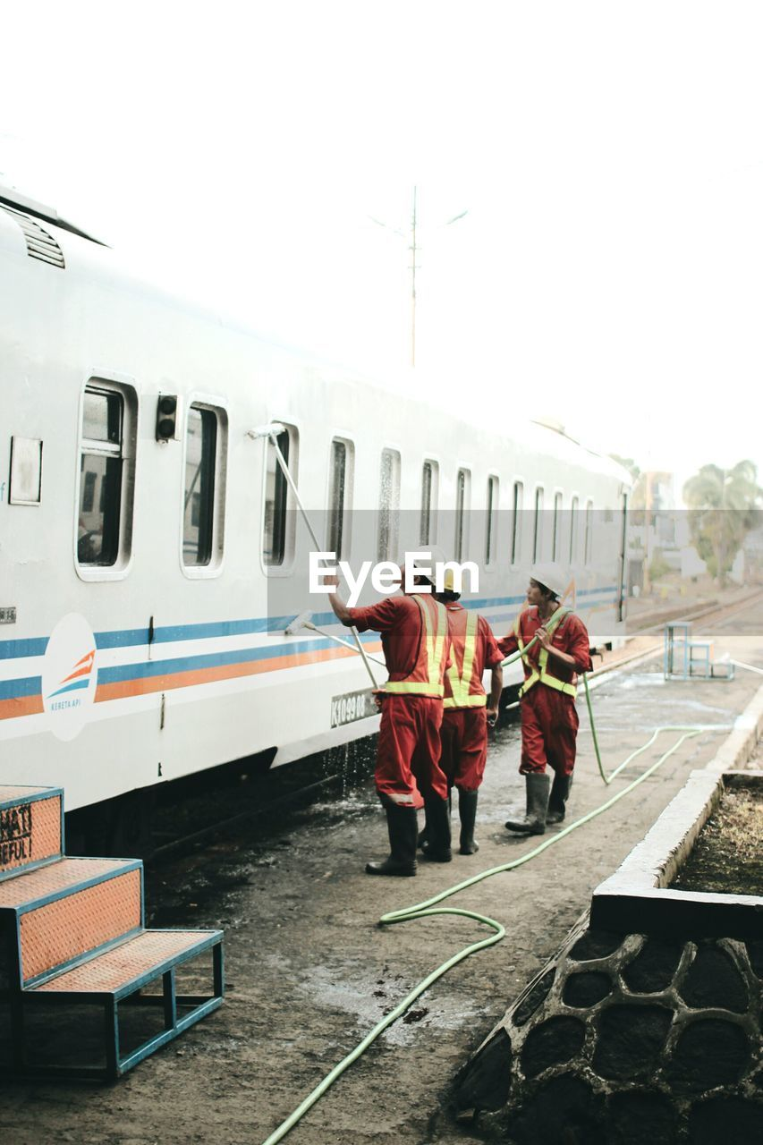 Full Length Men Washing Train Against Sky