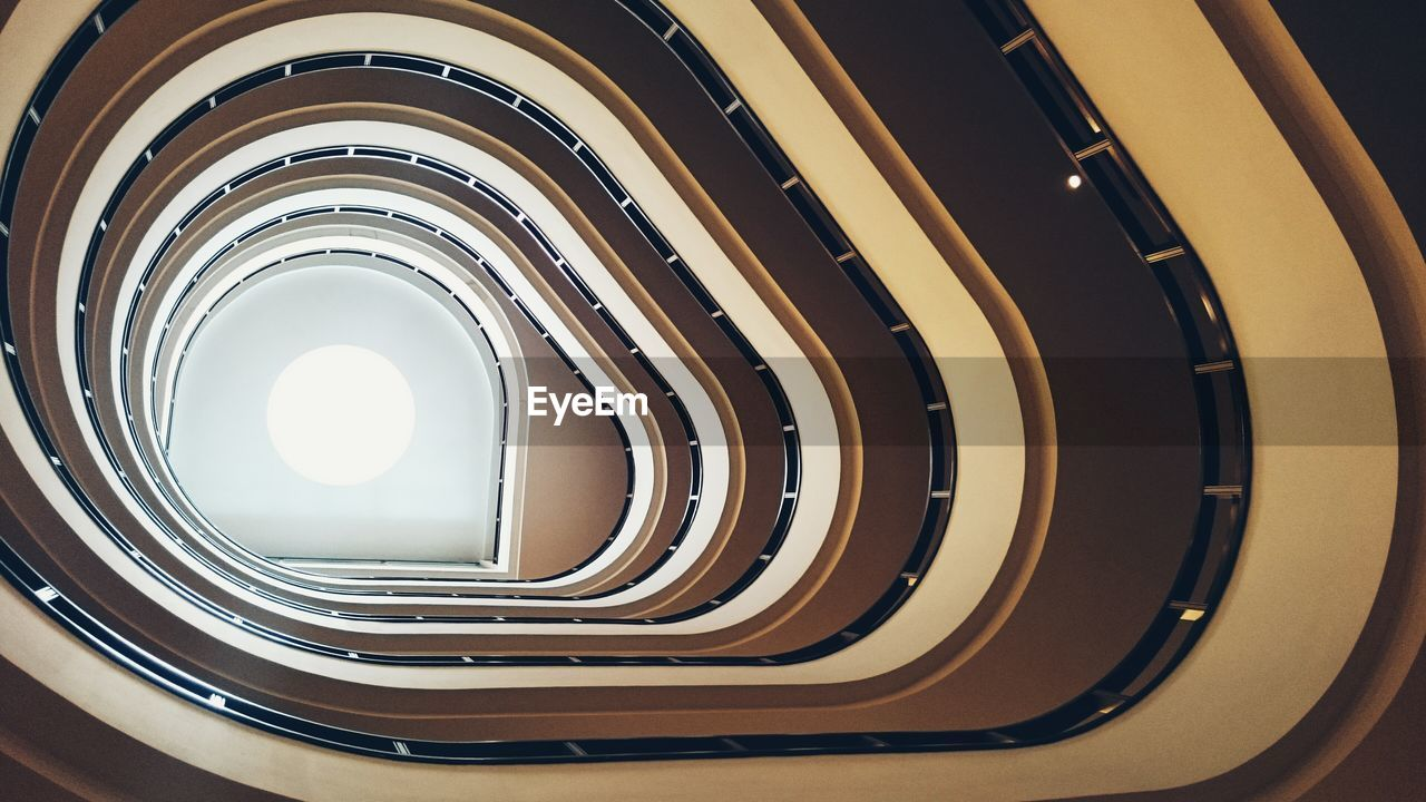 Directly Below Shot Of Spiral Staircase On Building Against Ceiling