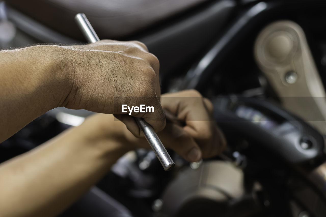 High angle view of man repairing car in garage