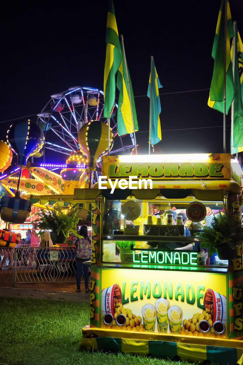 arts culture and entertainment, amusement park, illuminated, night, amusement park ride, leisure activity, group of people, outdoors, enjoyment, incidental people, fairground, text, multi colored, real people, nature, traveling carnival, communication, architecture, western script, nightlife