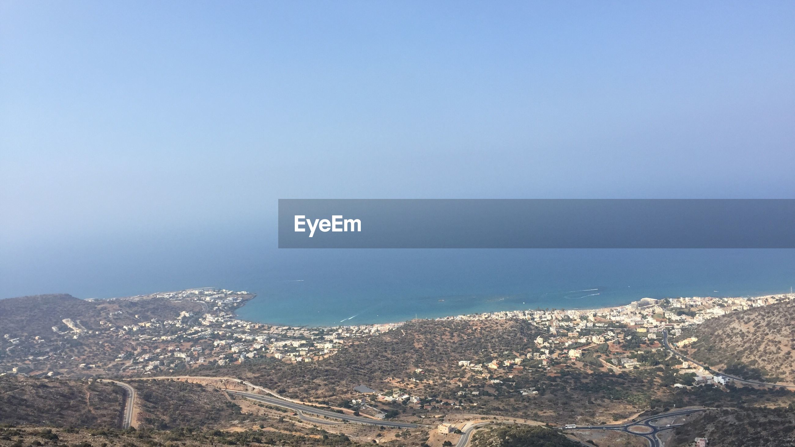 AERIAL VIEW OF SEA WITH CITYSCAPE IN BACKGROUND
