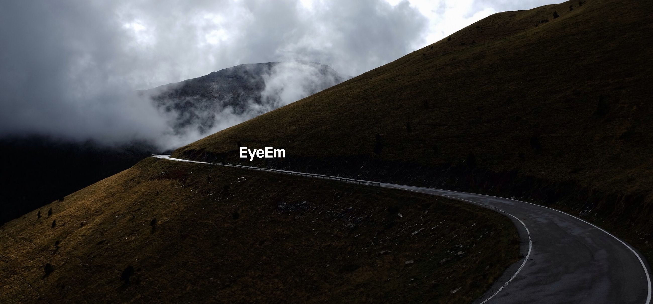 Mountain road against cloudy sky